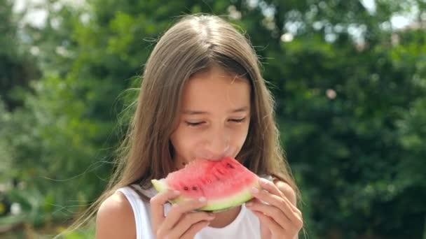 schöne kleine brünette Mädchen mit langen Haaren, die draußen eine Wassermelone essen. 4k. Zeitlupe.