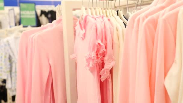 Oblečení na ramínkách v obchodu s módním zbožím. 4 k Zpomalený pohyb
