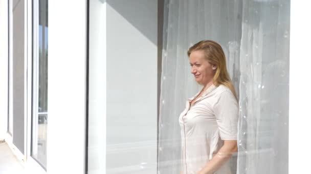 Atraktivní mladá žena otevře záclony v pomalém pohybu se dívá na východ stojící u okna v jejím domě. 4k