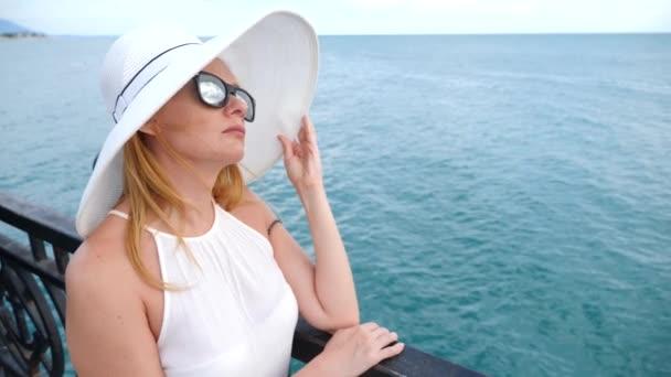 7e15442e4 Elegancka Kobieta w biały kapelusz z szerokim rondem i okulary szczyci się  widokiem na morze. 4k, zwolnionym tempie– filmik stockowy