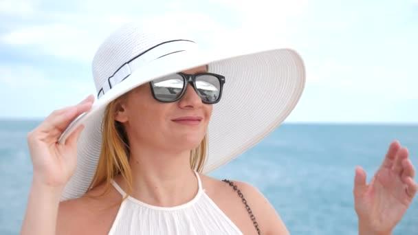 Eine elegante Frau in einem weißen breitkrempigen Hut und eine Sonnenbrille genießt den Blick aufs Meer. 4k, Zeitlupe