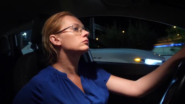 Frustrierte Frau steckt im Stau fest. Geschäftsfrau in der Nacht im Stau hinter dem Steuer eines Autos, vor einem Hintergrund von Autos. 4k. Zeitlupe
