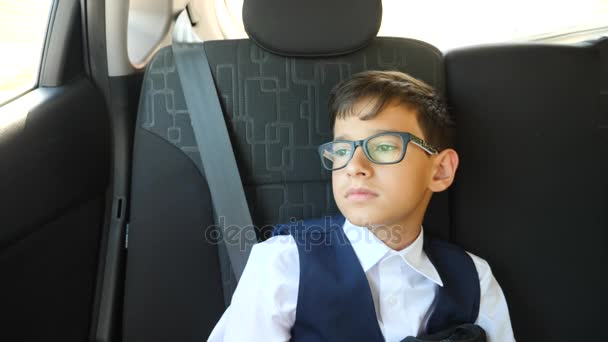 smutný kluk je jízda v autě v školní uniformu. 4k, pomalý pohyb