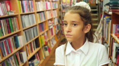 Portrait of a girl 8 - 12 years old, standing in the library. Bookshelves of a bookcase in the background. 4k, slow motion