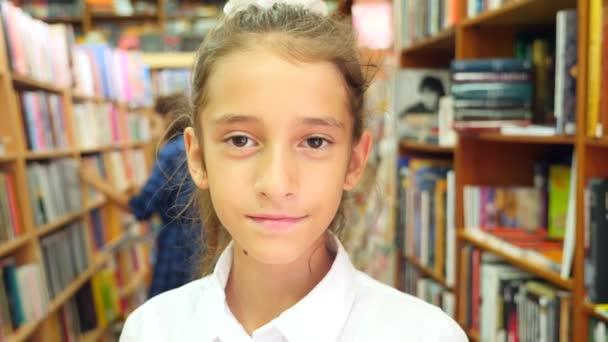 Portré egy lány, 8-12 éves korig, állandó a könyvtárban. Könyvespolcok a háttérben könyvespolc. 4k, lassú mozgás