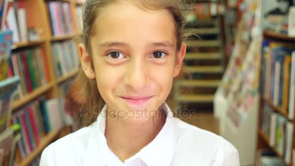 Portrét dívky 8-12 let starý, stojící v knihovně. Regály skříně v pozadí. 4k, pomalý pohyb