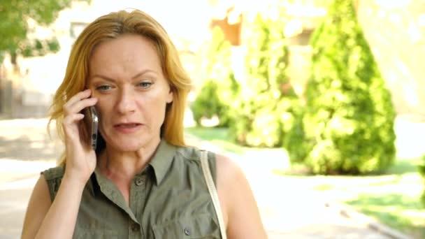Wütende Blondine telefoniert im Sommer in der Stadt, flucht und schreit, Kamera läuft herum. 4k. Zeitlupe