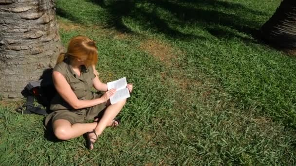 blonde woman reading the book in the park, sitting on the grass, under a tree. 4k, slow-motion