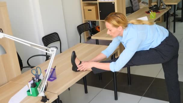 Female executive performing stretching at her workplace in office. 4k, slow motion