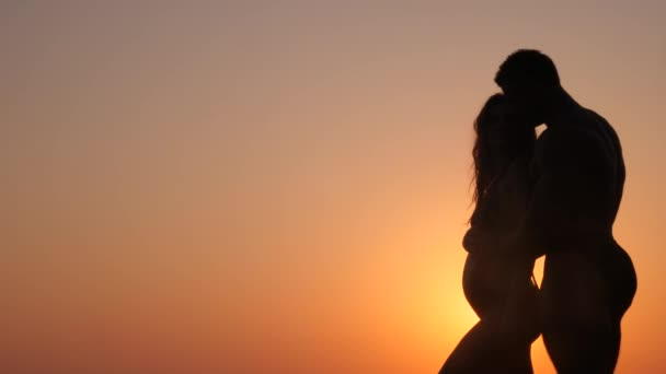Silhouettes of pregnant women in bikini and romantic muscular man. the bodybuilder hugs, kisses his wife and strokes her belly. against the background of a sea sunset. 4k. Slow motion