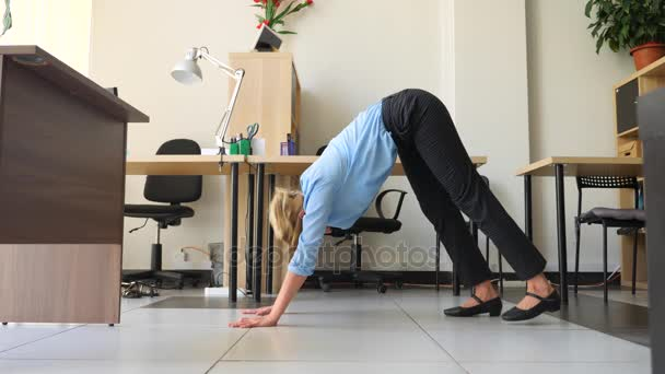 Female executive performing yoga at her workplace in office. 4k, slow motion
