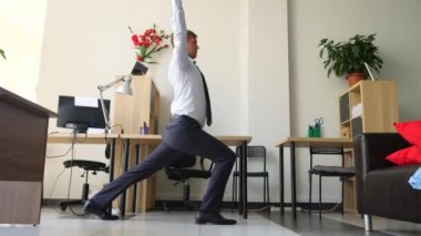 male executive performing yoga at her workplace in office. 4k, slow motion