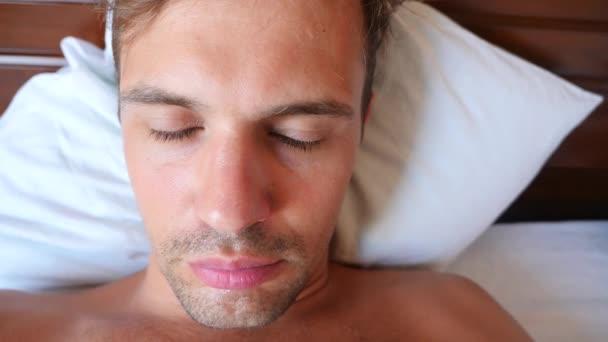 Portrét mladého muže s hloupé grimasy, ležící na posteli. 4 k Zpomalený pohyb