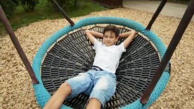 boy swinging on a swing a hammock on the amusement park in the city  4k cute children boy brothers swinging on a big rope swing in      rh   depositphotos