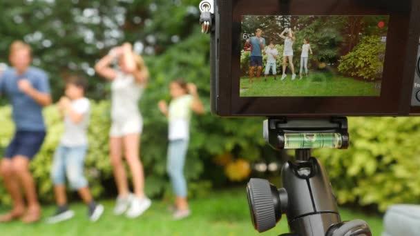 nahrávat video na kameru rodina. Šťastná rodina tančí spolu na trávě v parku s krásnou přírodou. 4 k. kopie prostor. životní styl. Zpomalený pohyb
