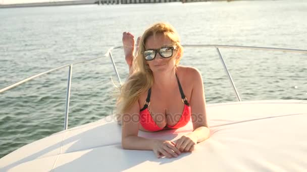 Attractive woman on a yacht on a summer day at sea. slim busty blonde with long hair, wearing sunglasses and a bright red bikini is sunbathing on the deck of a boat in the open sea. slow motion