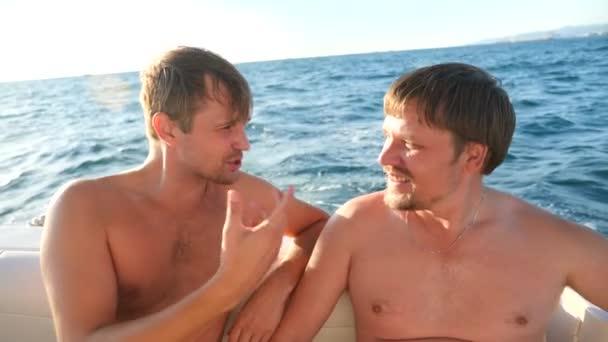 két vidám meg egy jachton a tengerben úszó, ölelés, és mosolyog. 4k, lassú mozgás