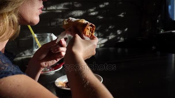 Donna affamata, divertente mangiare gustoso dessert in caffetteria. 4K, rallentatore
