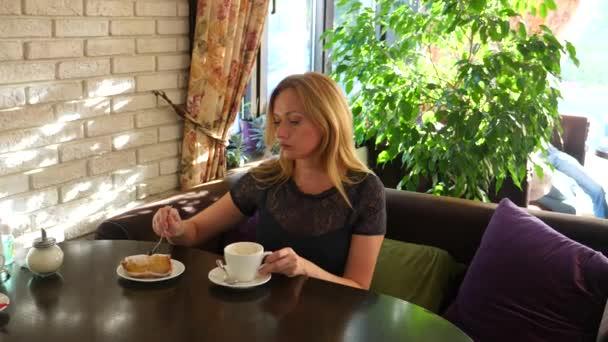 Hlad, zábavný žena jíst chutné dezert v kavárně. 4k, pomalý pohyb