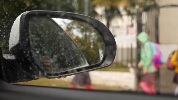 Elementary-school students return home after lessons. Students go home. meeting the child after school by car. 4k, slow motion. Drops on the car mirror .