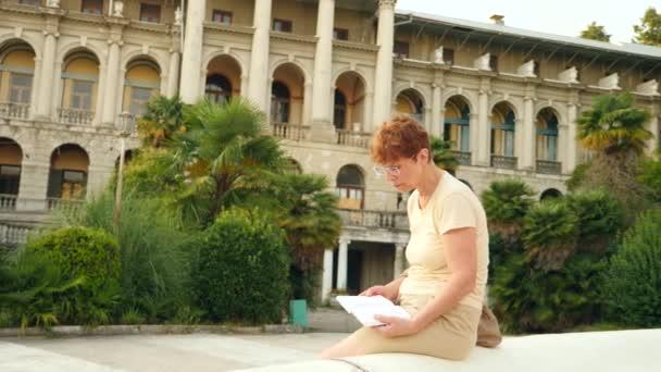 Milé starší paní sedí na lavičce v městském parku. čte knihu papíře. 4. Slow-motion