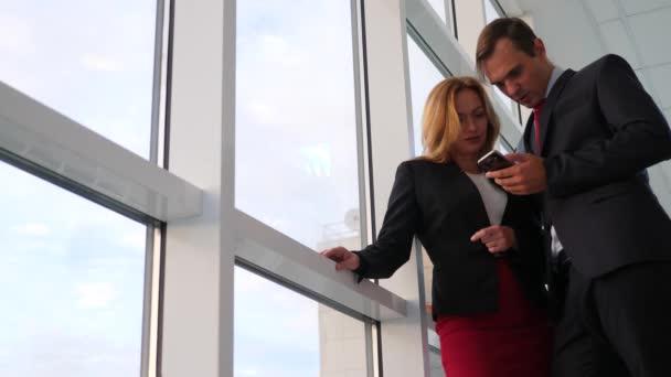 Mann und Frau in Anzügen stehen und reden. Geschäftsfrau und Geschäftsfrau stehen im Büroflur vor dem Fenster. 4k, Zeitlupe
