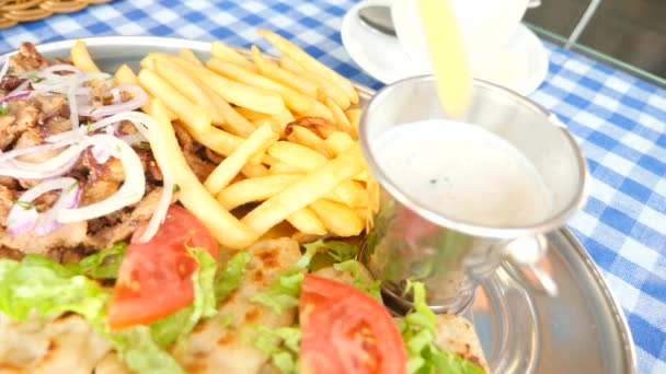close-up, mens hands eat Greek souvlaki. dips a piece of French fries into a white sauce. 4k, slow motion