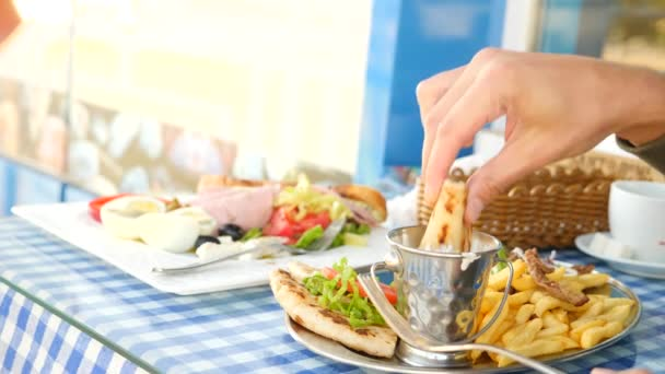 close-up, mens hands eat Greek souvlaki. dipping a piece of cake into a white sauce. 4k, slow motion