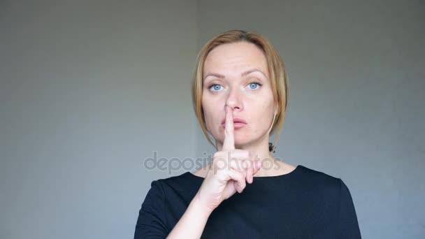 4 k. zblízka krásná blondýnka s jasně modrýma očima. portrét mladé ženy. řeč těla a gesta. položila si prst ke rtům, tišeji