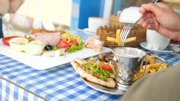 Romantický pár jíst v venkovní kavárna řecká jídla, suvláki a řecký snídaně. 4k, pomalý pohyb