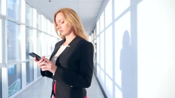 az üzleti üzletasszony ruha egy okostelefon, séta a folyosón, a business center panoráma ablakos, 4k, lassú mozgás, a tér a másolás