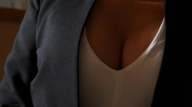 A woman with a beautiful chest puts on a black jacket. 4k, slow motion