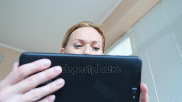 4 k. zpomaleně. mladá žena při pohledu na tabletu překvapený oči makro zblízka,