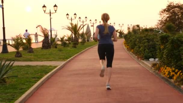 Road runner žena běží v parku u běhání palm grove, běžící žena venku, v parku s palmami, násep, v létě. 4 k Zpomalený pohyb