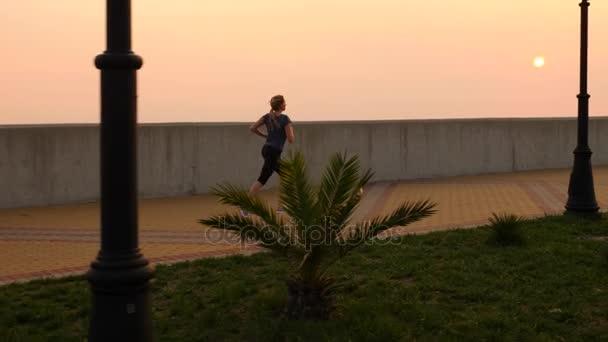Road runner nő fut park, jogging palm grove mentén futó nő szabadban, Park, pálmafák, a töltésen, a nyáron. 4 k-lassú mozgás