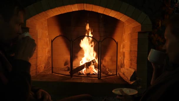 Fire in a fireplace  4k, slow motion  man and woman drink tea near the  fireplace