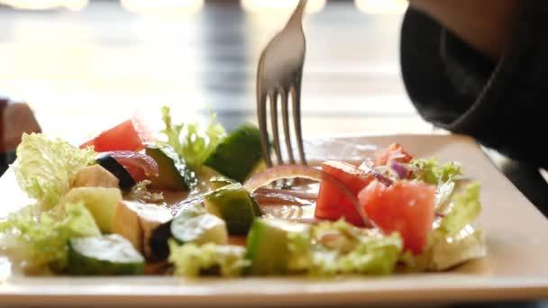 někdo jí Řecký salát v restauraci rychlého občerstvení. 4k, Zpomalený detail