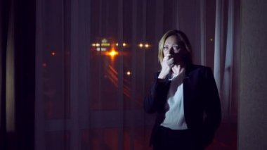 Woman in a business suit eating an apple standing by the night panoramic window. view of the city, night lights. 4k