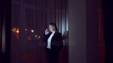Young woman in a business suit drinking beverage standing by the window at home at night. Panorama window, view of the city, night lights. 4k