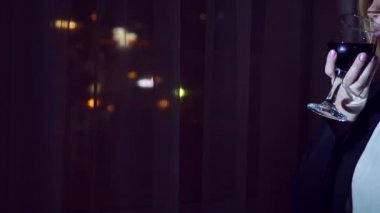 A young woman in a business suit is drinking red wine, standing at the window of a house at night. Window panorama, view of the city, night lights. 4k