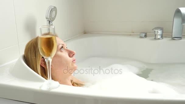 žena blond pití vína ve vaně. 4k, pomalý pohyb