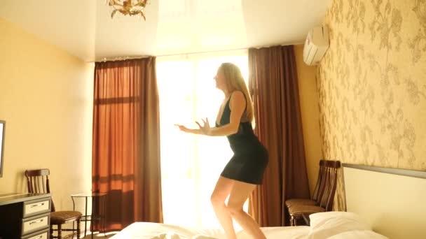 Žena skáče a tančí na posteli pro radost, zpomalené. 4k