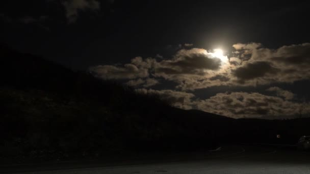 Time Lapse: Full moon in the night sky against the backdrop of the track. turn for a mountain. 4k