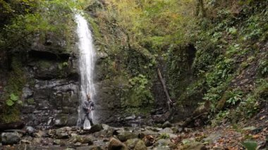 Happy man backpacker enjoying amazing tropical waterfall.Travel Lifestyle and success concept vacations into the wild nature on background mountain. 4k, slow motion