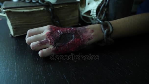 Hrozné rukou s krvavé rány je zřetězené Železný řetěz. Ruční monstrum na halloween. 4k, pomalý pohyb