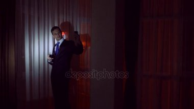 A young man in a business suit drinks alcohol, and makes selfie on his smartphone, stands at the window of the house at night. Window panorama, view of the city, night lights. 4k