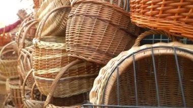A woman chooses a wicker basket at a folk craft fair. 4k, slow motion