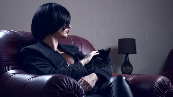 heiße Brünette mit runder Sonnenbrille, sitzt in einem Sessel und streichelt eine schwarze Katze. 4k, Zeitlupe