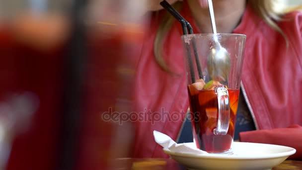 Die schöne Frau ruht sich in einem Café aus, trinkt heißen Glühwein und blickt in ihr Smartphone. 4k, Hintergrund verschwommen.