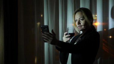 A woman in a business suit drinks alcohol, and makes selfie on his smartphone, stands at the window of the house at night. Window panorama, view of the city, night lights. 4k